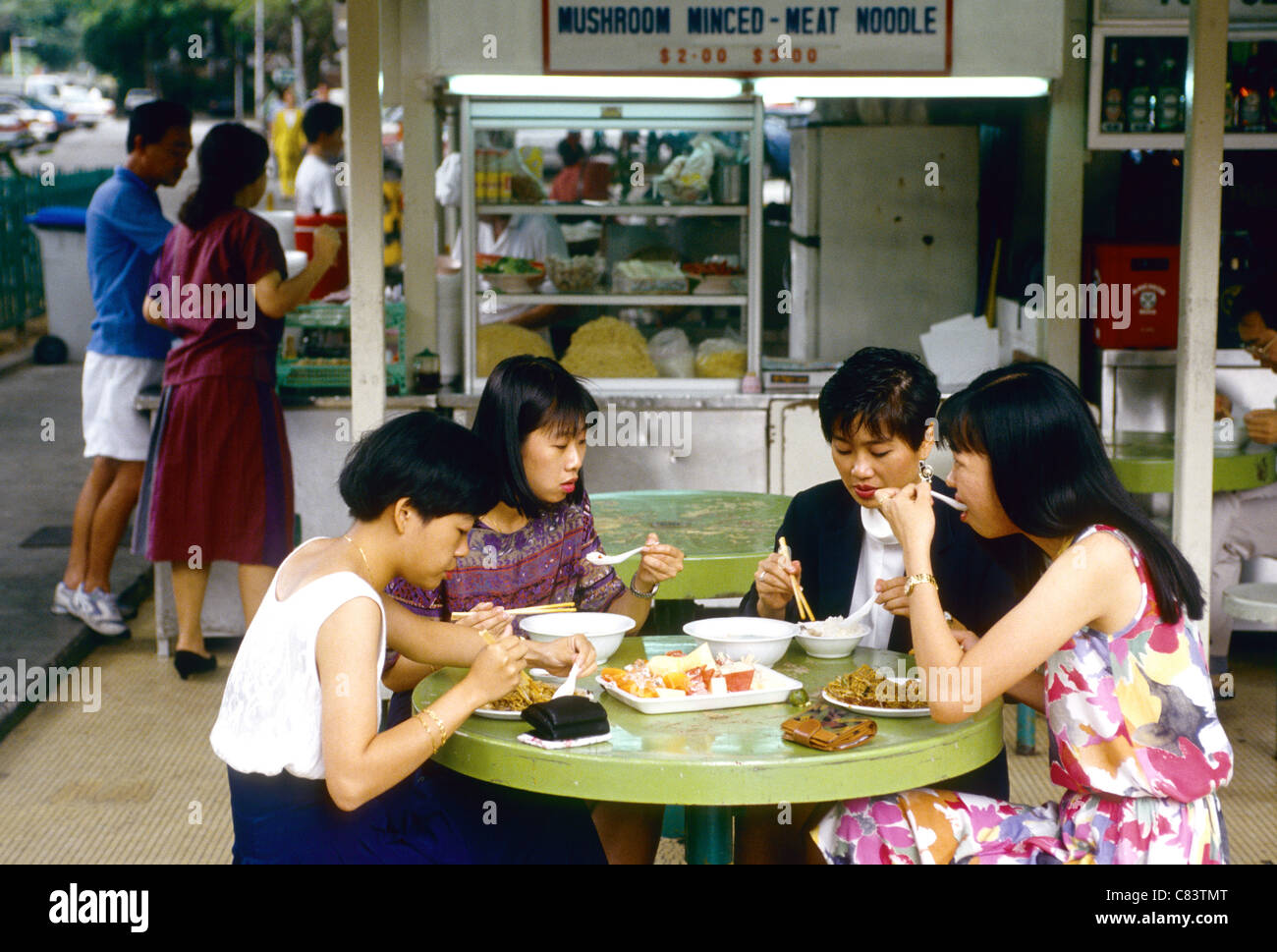Four young women offfice workers take lunch at a characteristic street restaurant in Singapore South East ASia - Stock Image