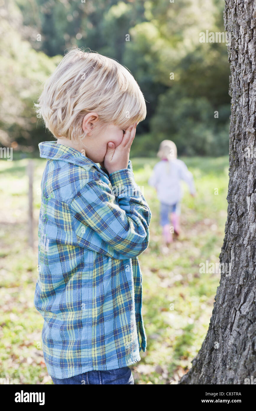 Children playing hide and seek outdoors Stock Photo