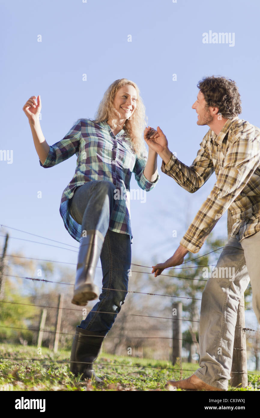 Couple climbing over wire fence outdoors - Stock Image