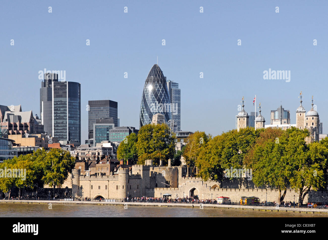 Urban landscape beyond River Thames with City of London skyline & medieval Tower of London contrasting with - Stock Image