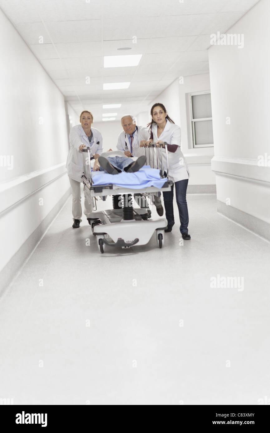 Doctors wheeling patient down hallway - Stock Image