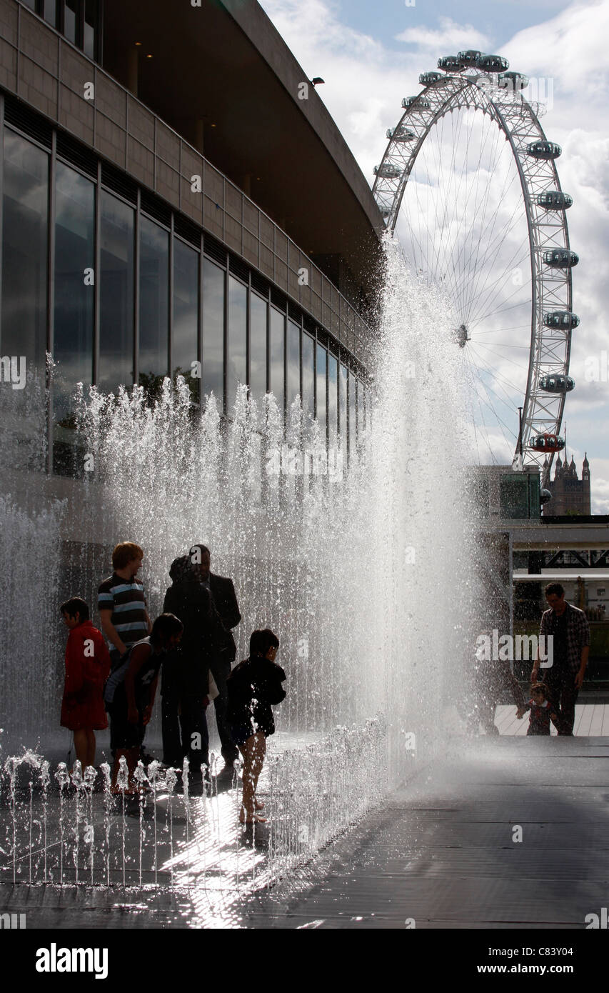 Playing in the Appearing Rooms fountains outside the Festival Hall on London's South Bank Stock Photo