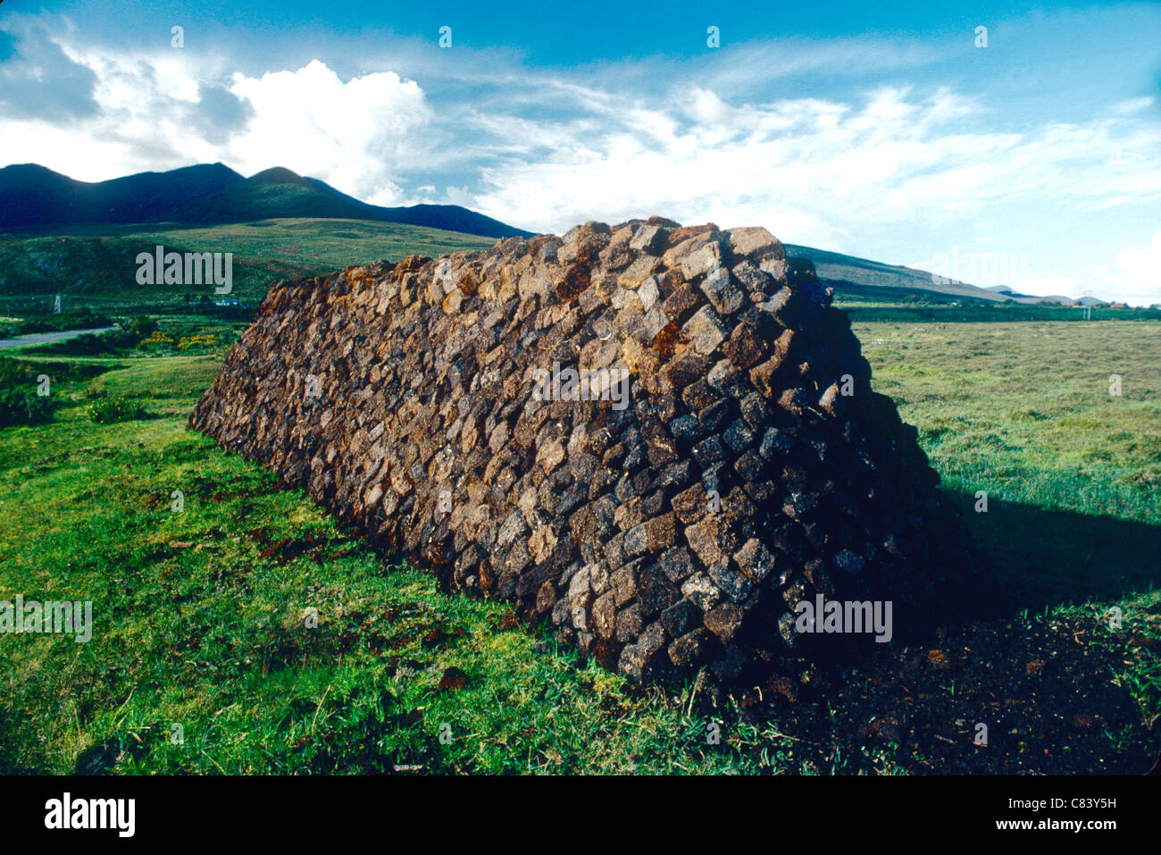 A well carefully stacked clamp of Turf (peat)  in a Connemara landscape in the west of Ireland - Stock Image