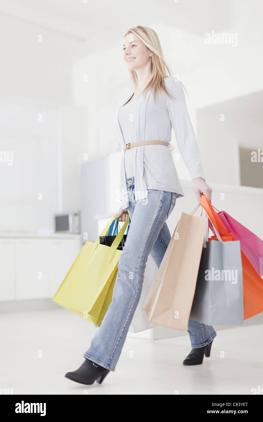 Smiling woman carrying shopping bags - Stock Image