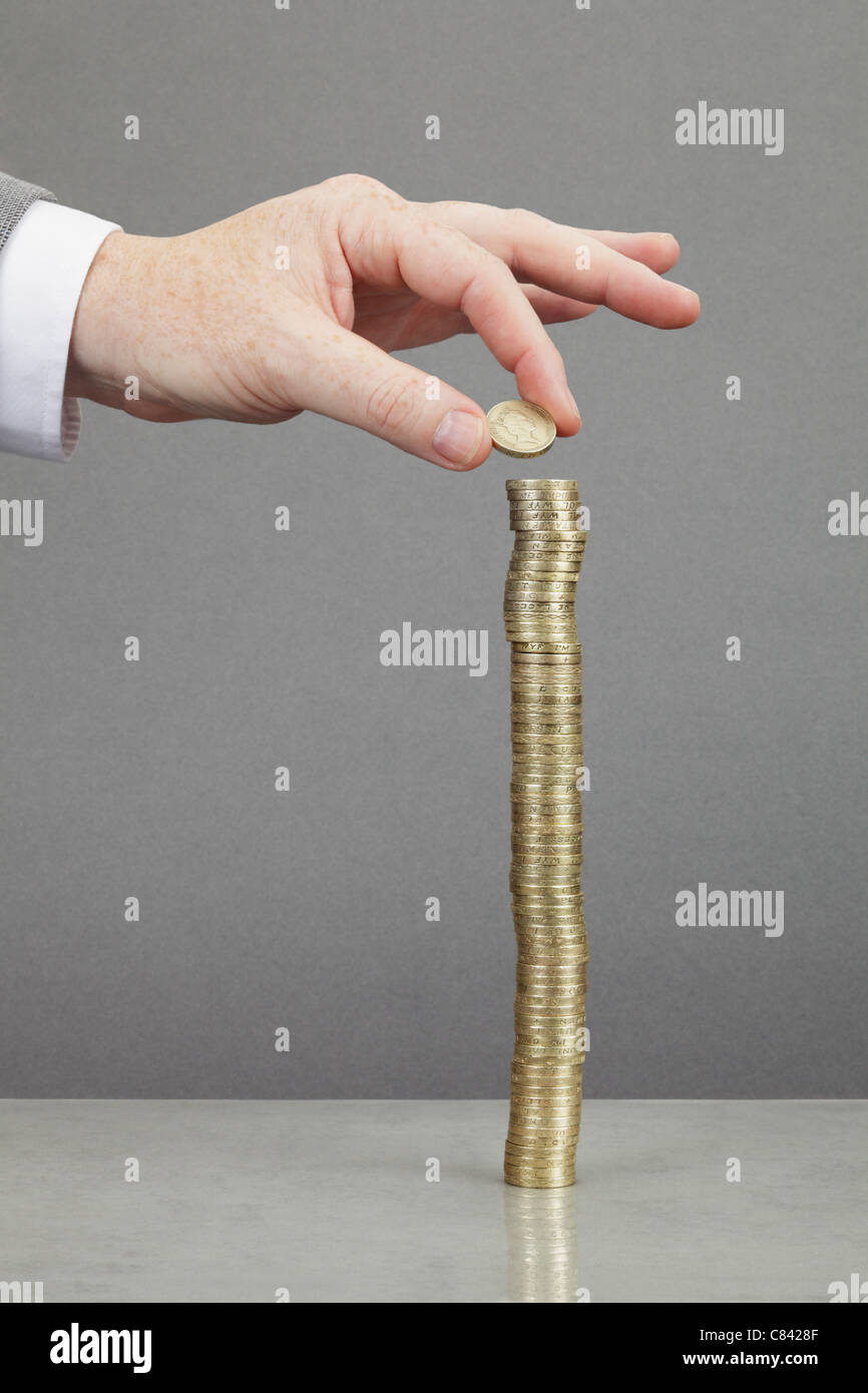 Businessman making stack of coins - Stock Image