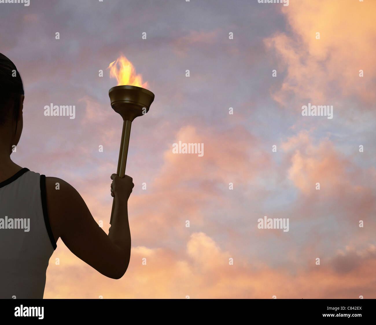 Athlete holding flaming baton - Stock Image