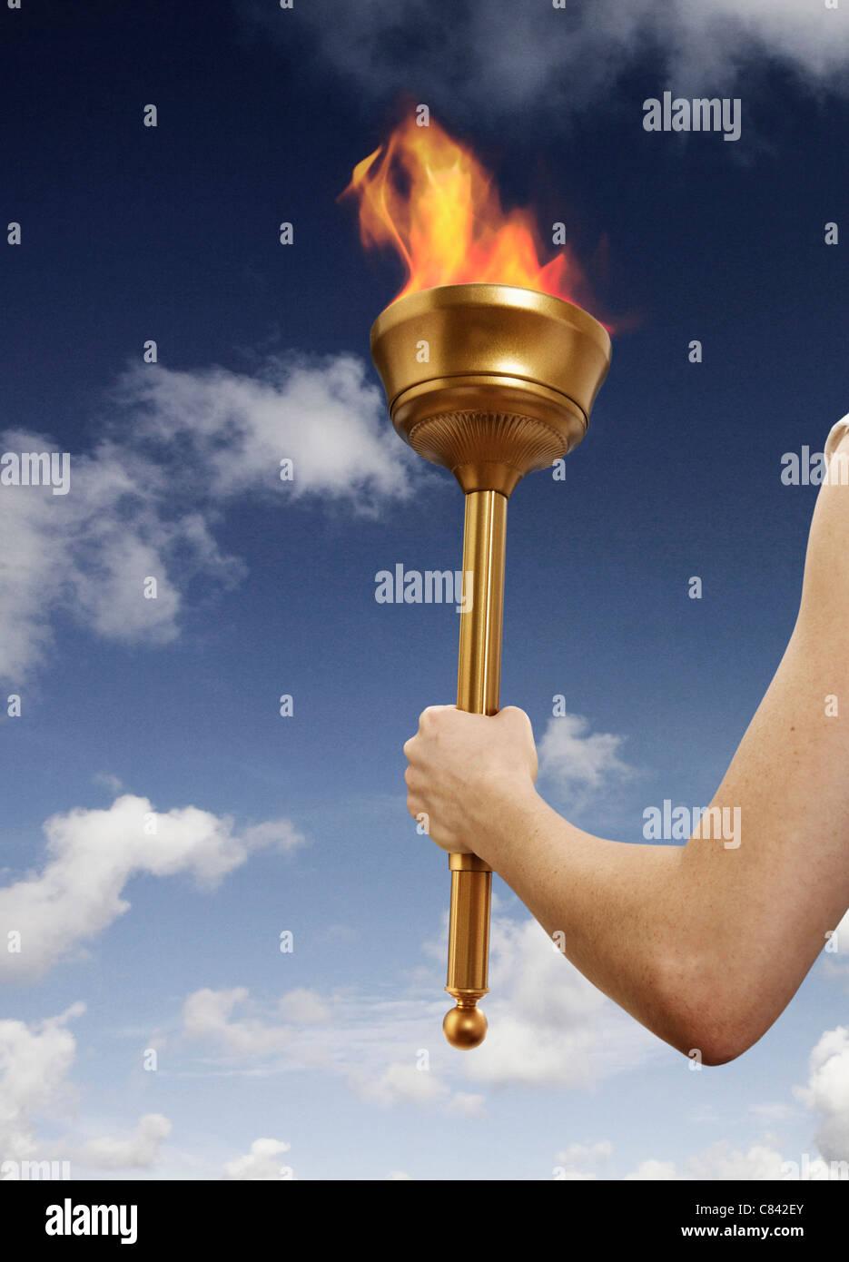 Hand holding flaming baton - Stock Image