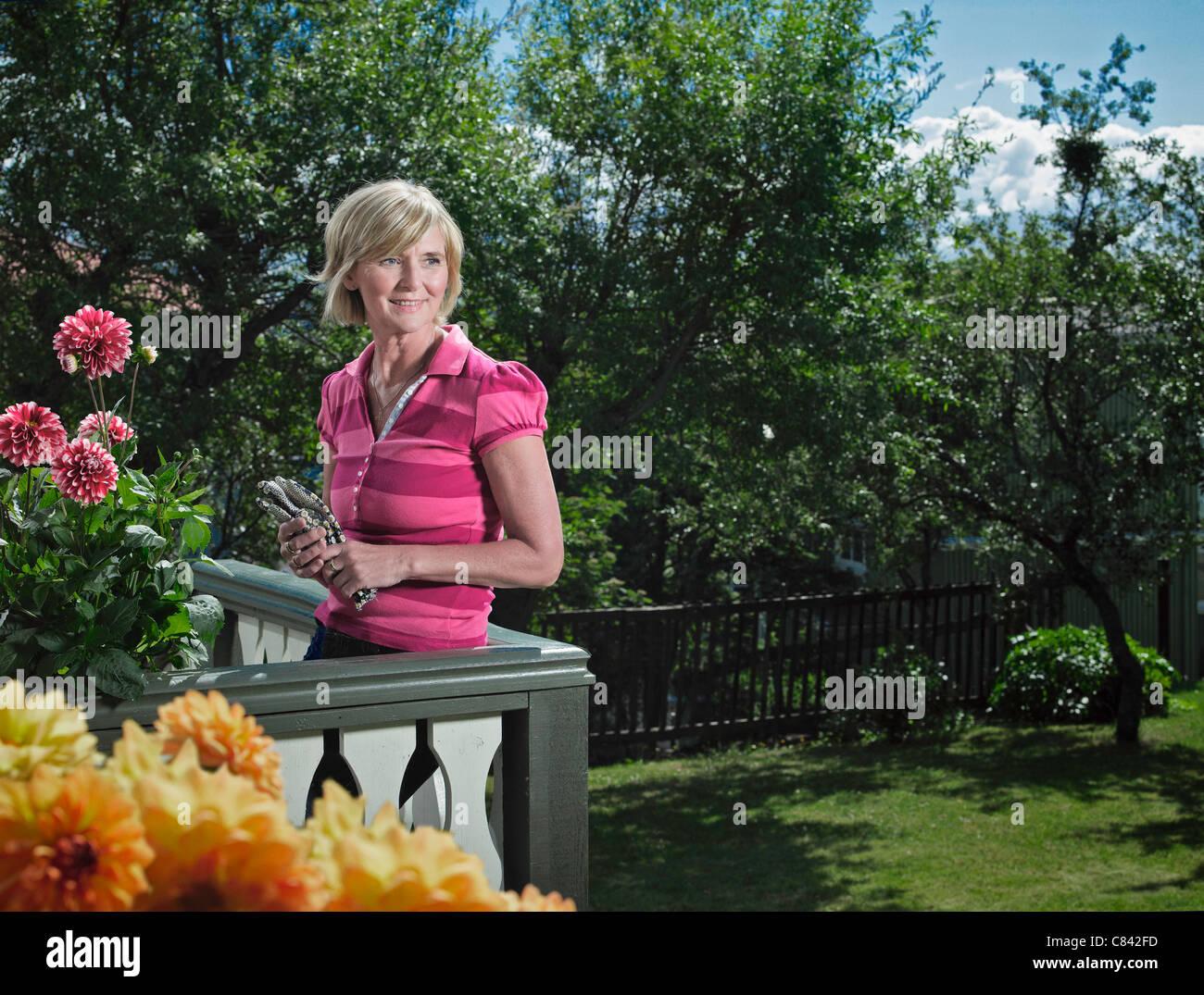 Woman relaxing on balcony - Stock Image