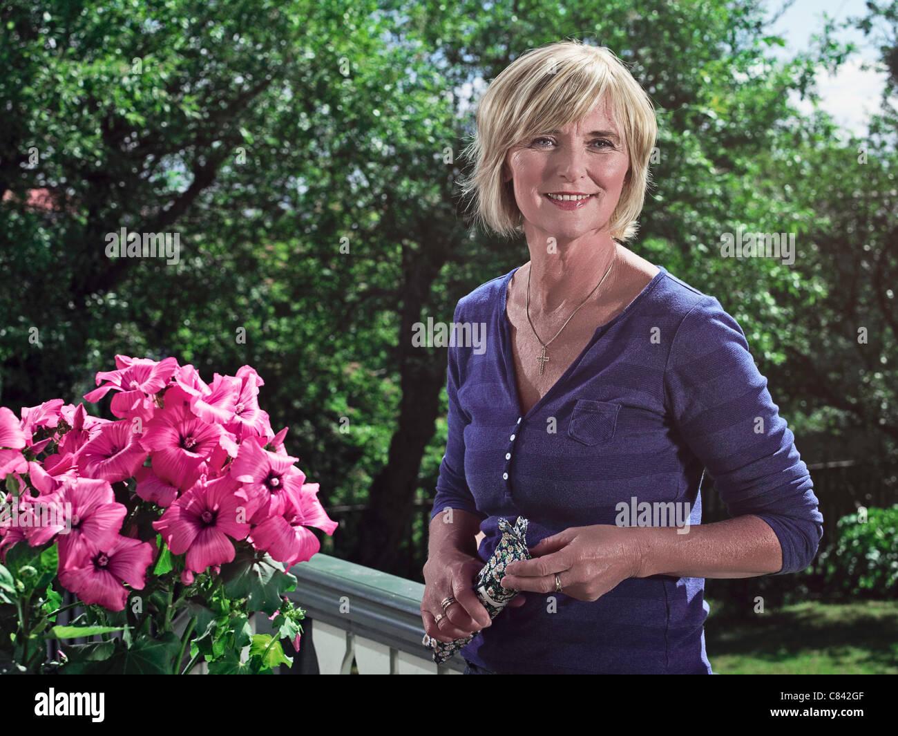 Woman smiling on balcony - Stock Image