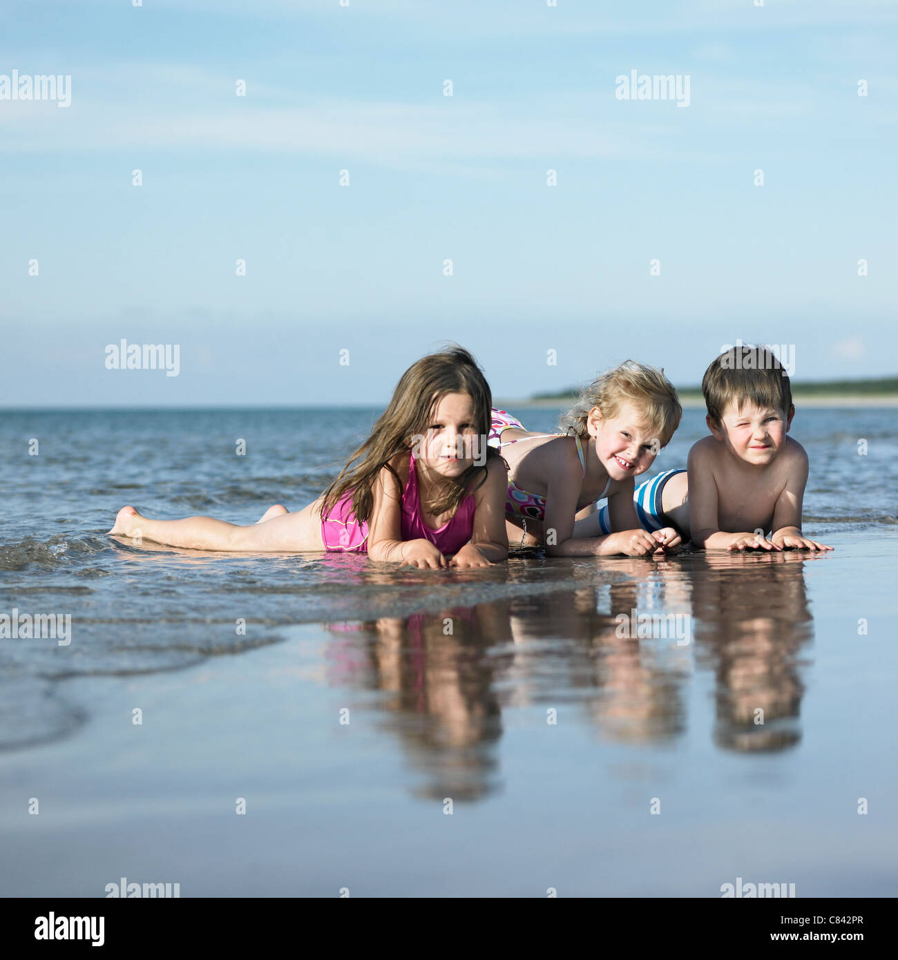 Children playing in waves on beach Stock Photo