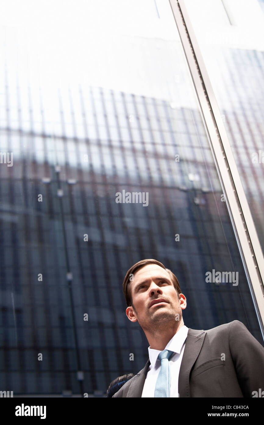 Businessman standing next to high rise - Stock Image