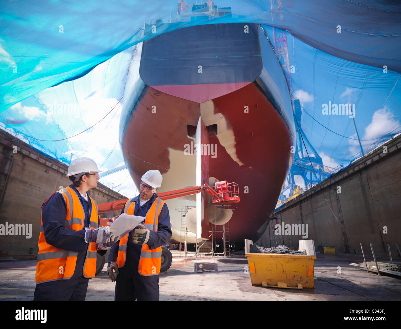Workers talking at shipbuilding site - Stock Image