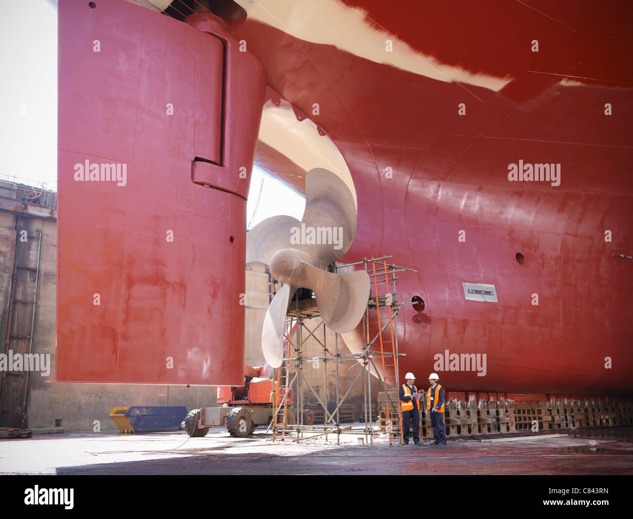 Workers talking on shipbuilding site - Stock Image