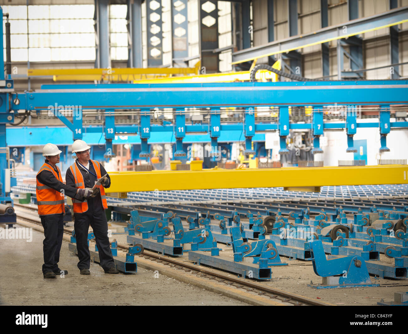 Workers examining shipbuilding machinery - Stock Image