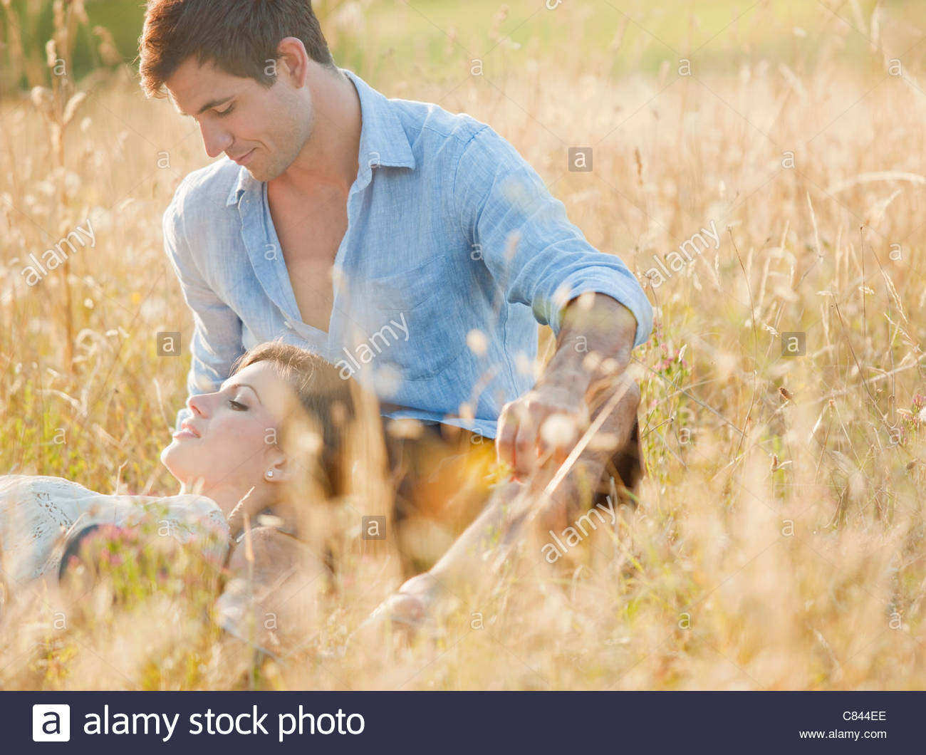 Smiling couple relaxing in wheatfield - Stock Image