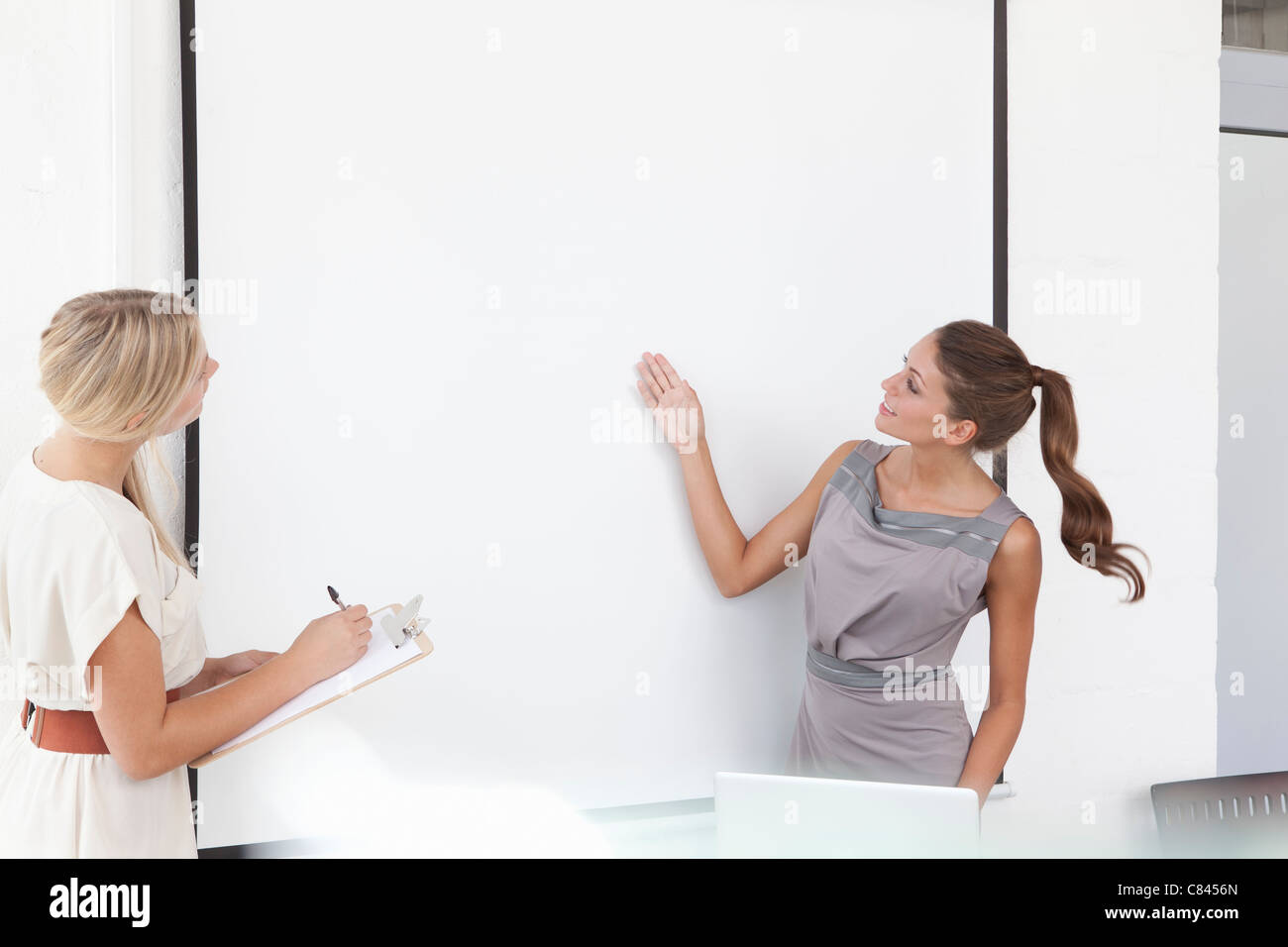 Businesswomen examining screen in office - Stock Image