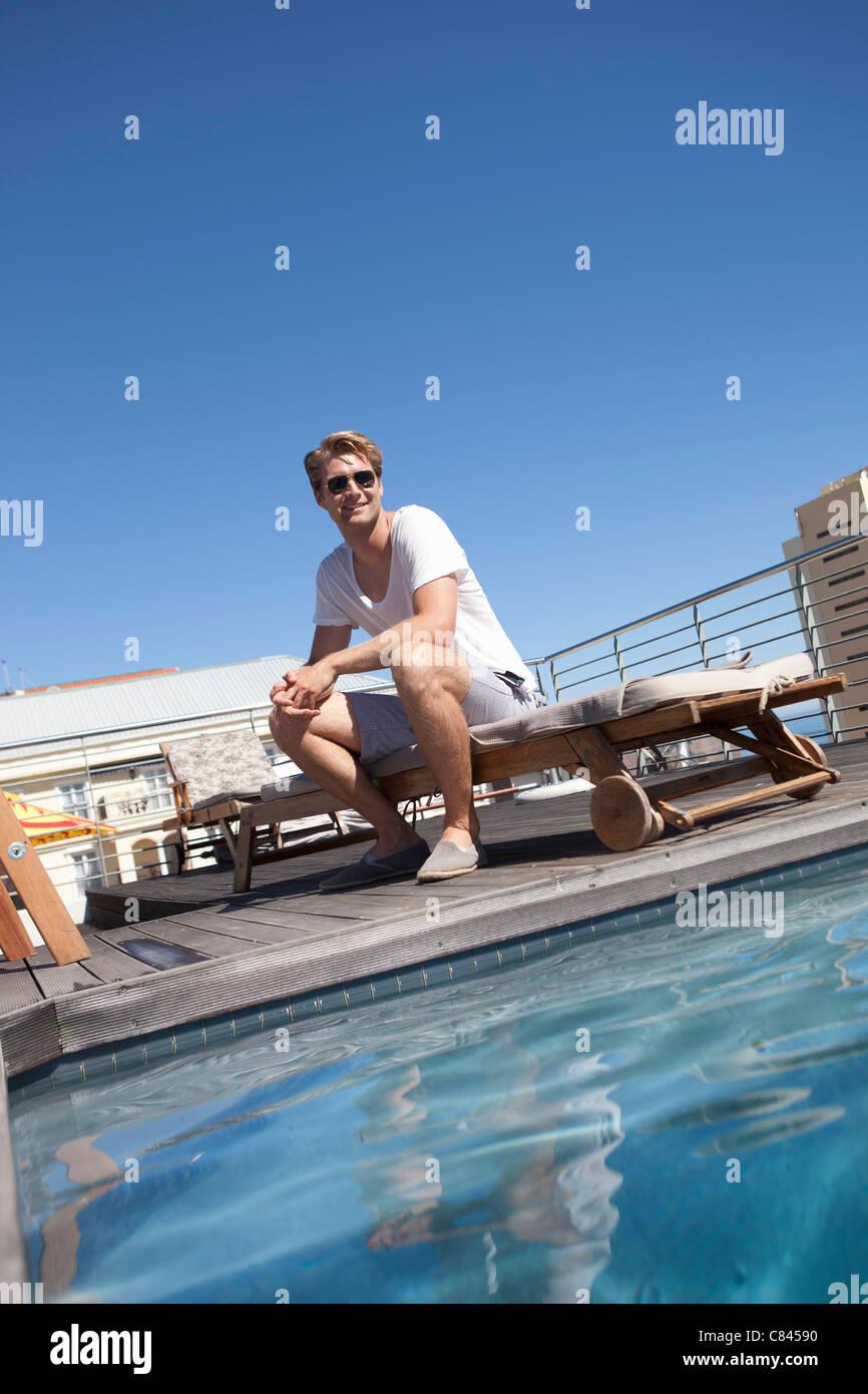 Man sitting by swimming pool Stock Photo