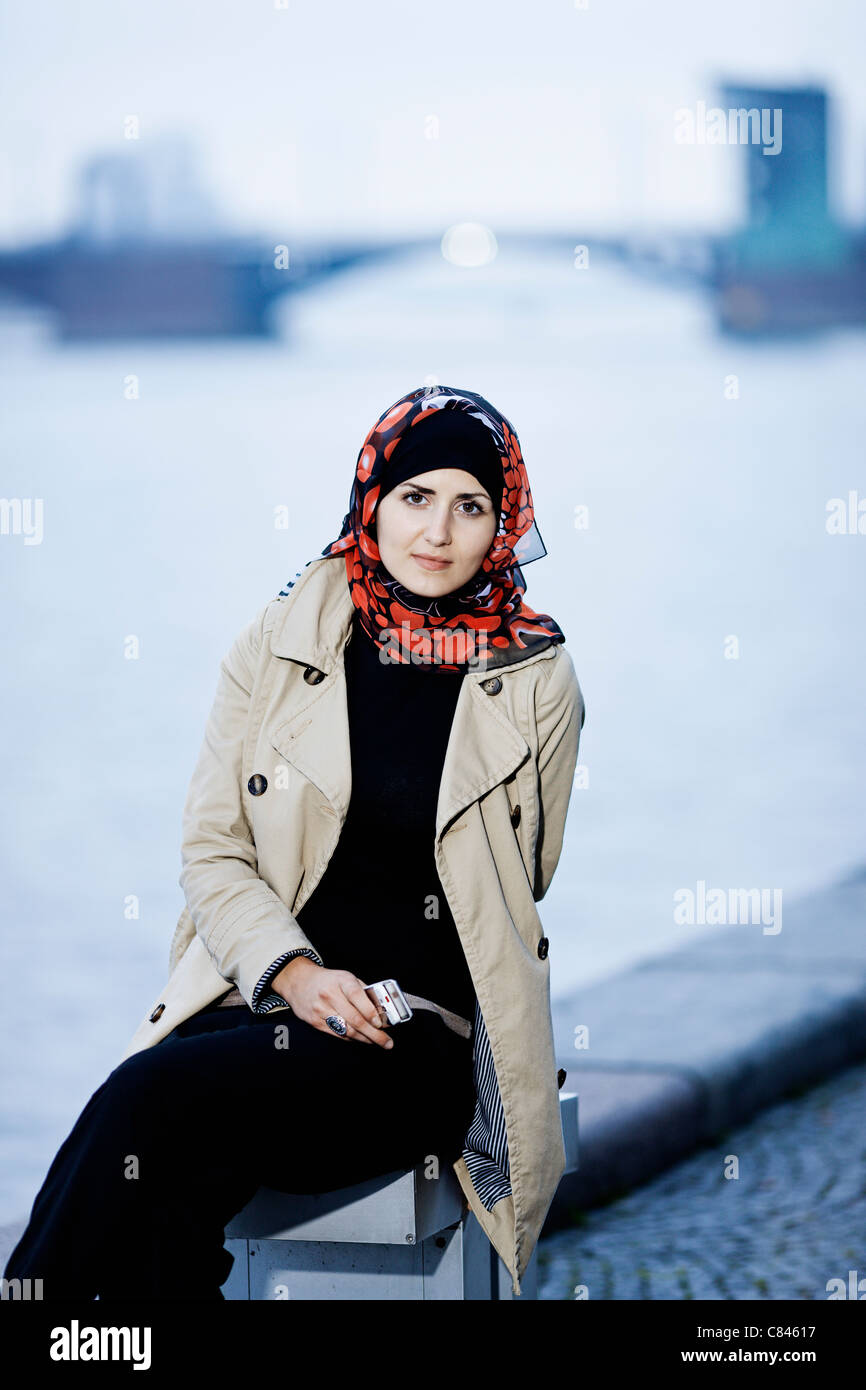 Woman in headscarf sitting on bench Stock Photo