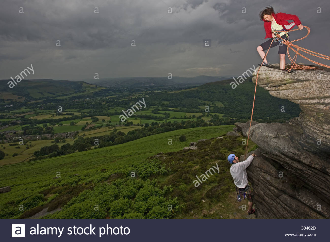 Rock climbers scaling steep rock face - Stock Image