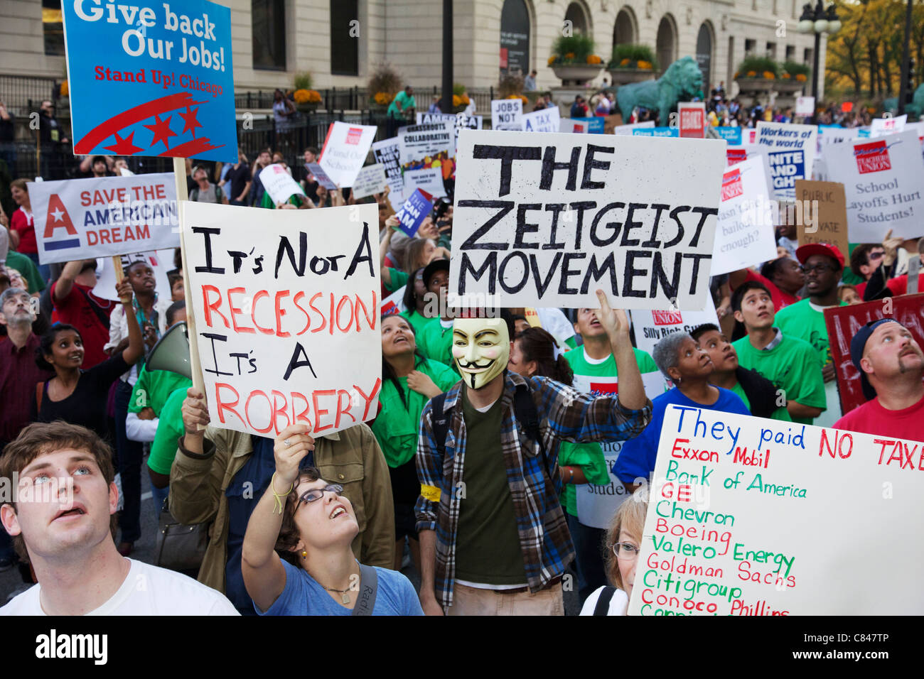 Protesters marching on Michigan Avenue, one wearing Guy Fawkes mask. Occupy Chicago protest. - Stock Image