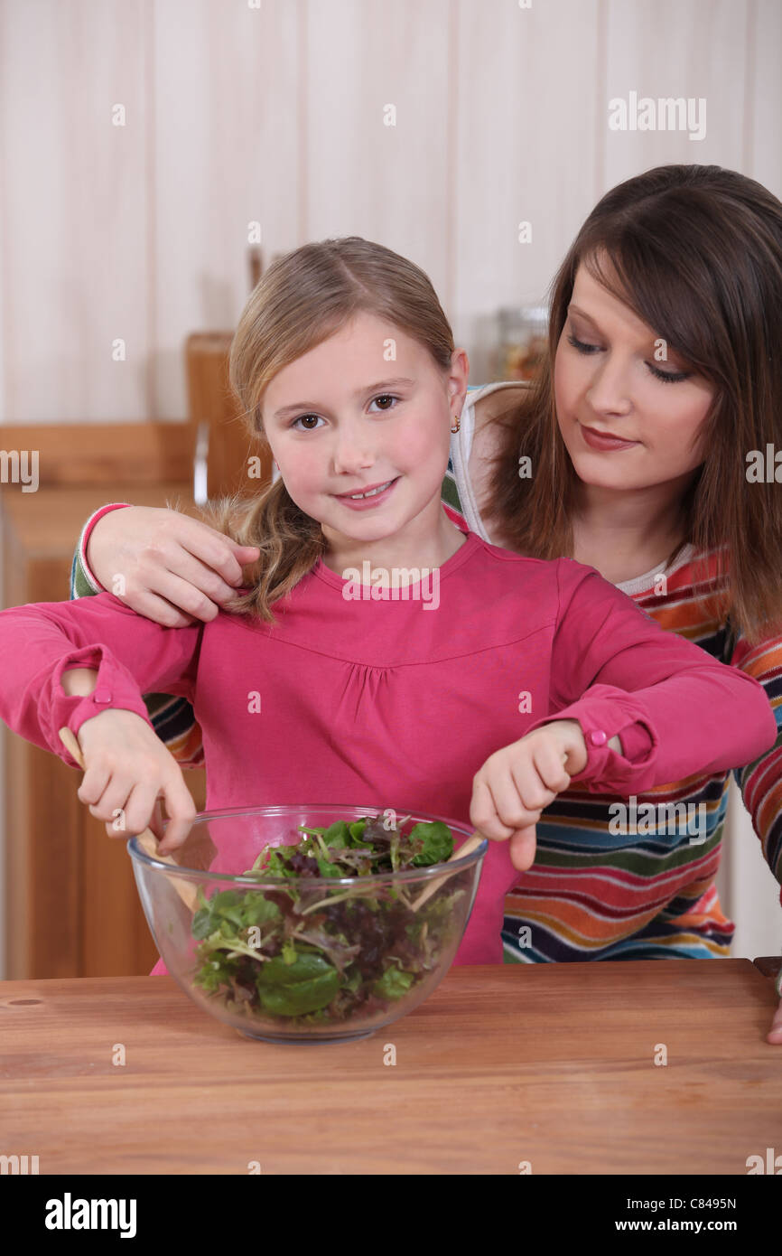 Mother and daughter making salad - Stock Image