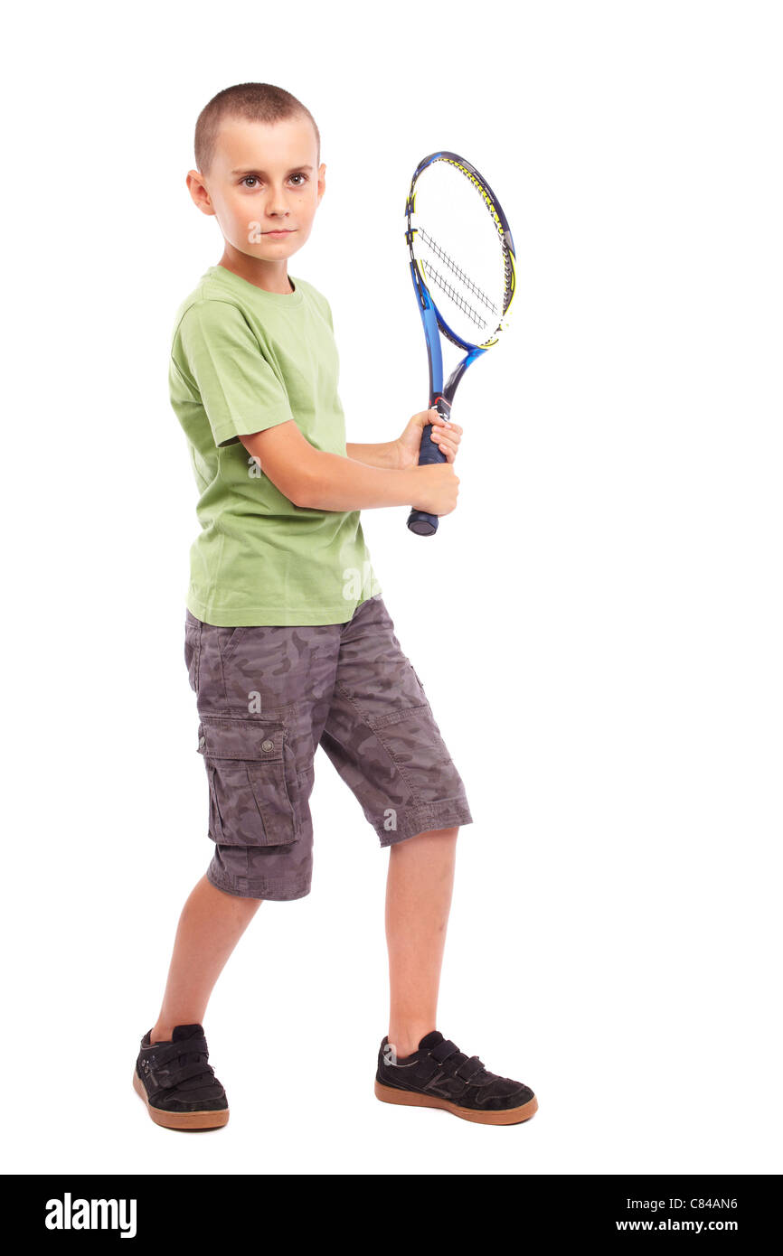 Child playing training with a field tennis racquet, studio full length portrait - Stock Image