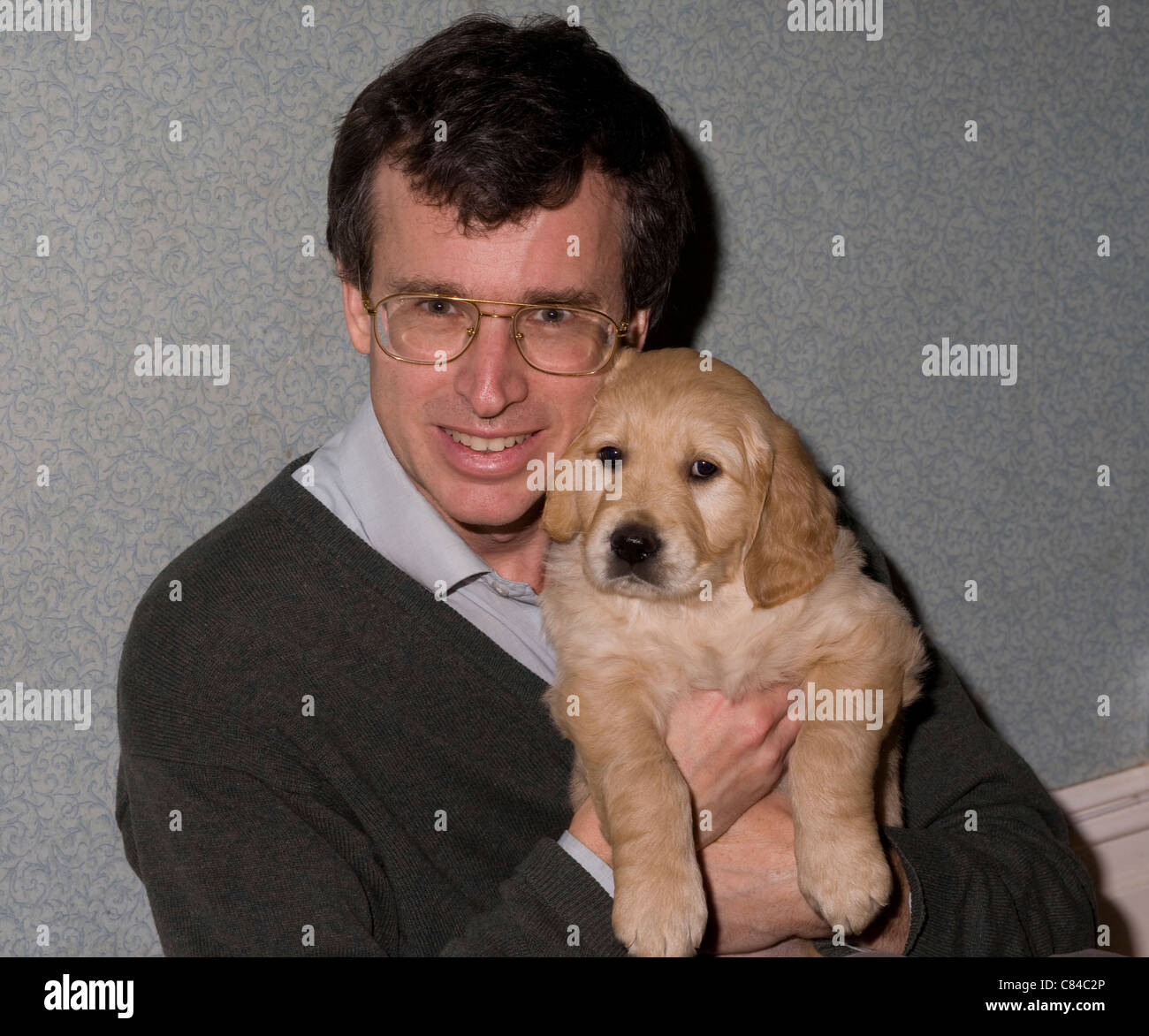 Breeder holds Baxter, a golden retriever dog puppy destined for training as an assistance dog with Dogs for the - Stock Image