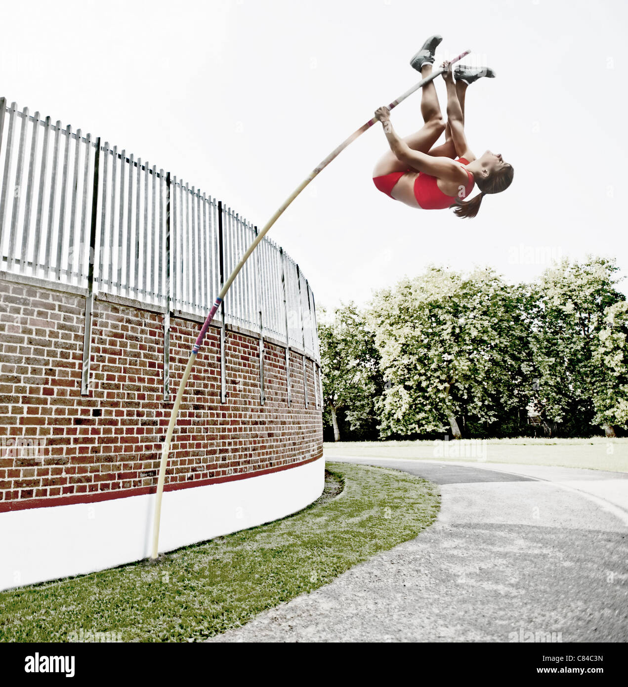 Athlete vaulting over brick wall - Stock Image