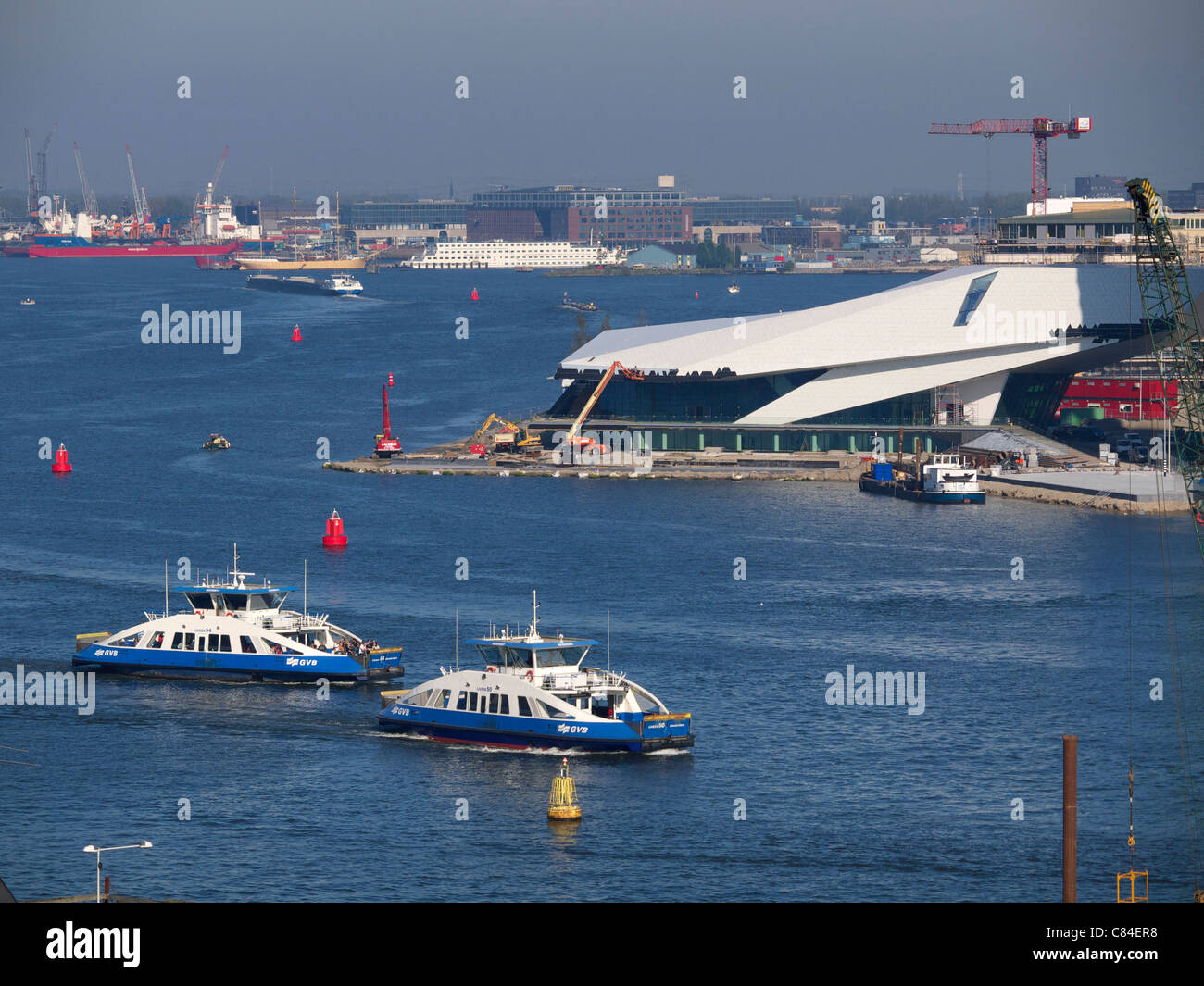 the IJ water with ferries and new museum being built in Amsterdam north, the Netherlands - Stock Image