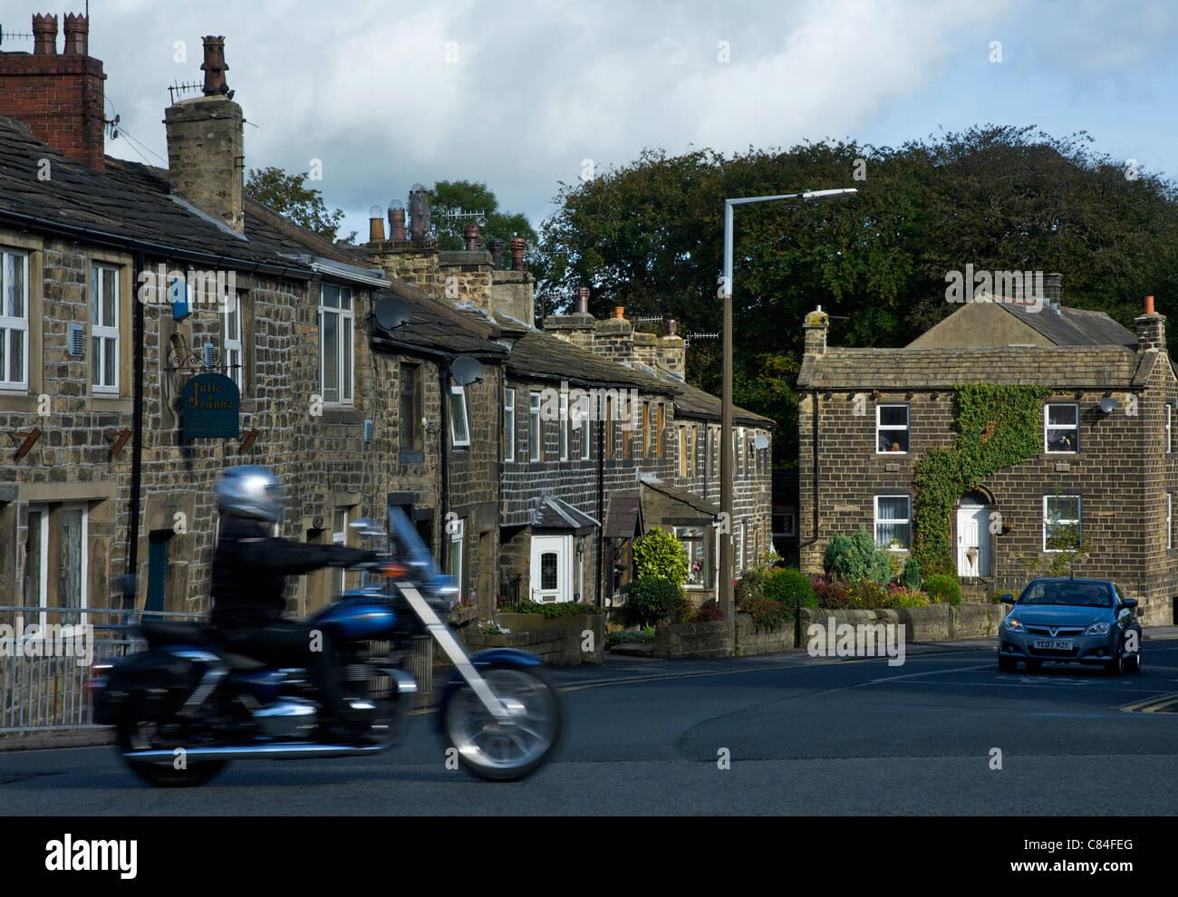 Biker passing through the village of Steeton, West Yorkshire, England UK - Stock Image