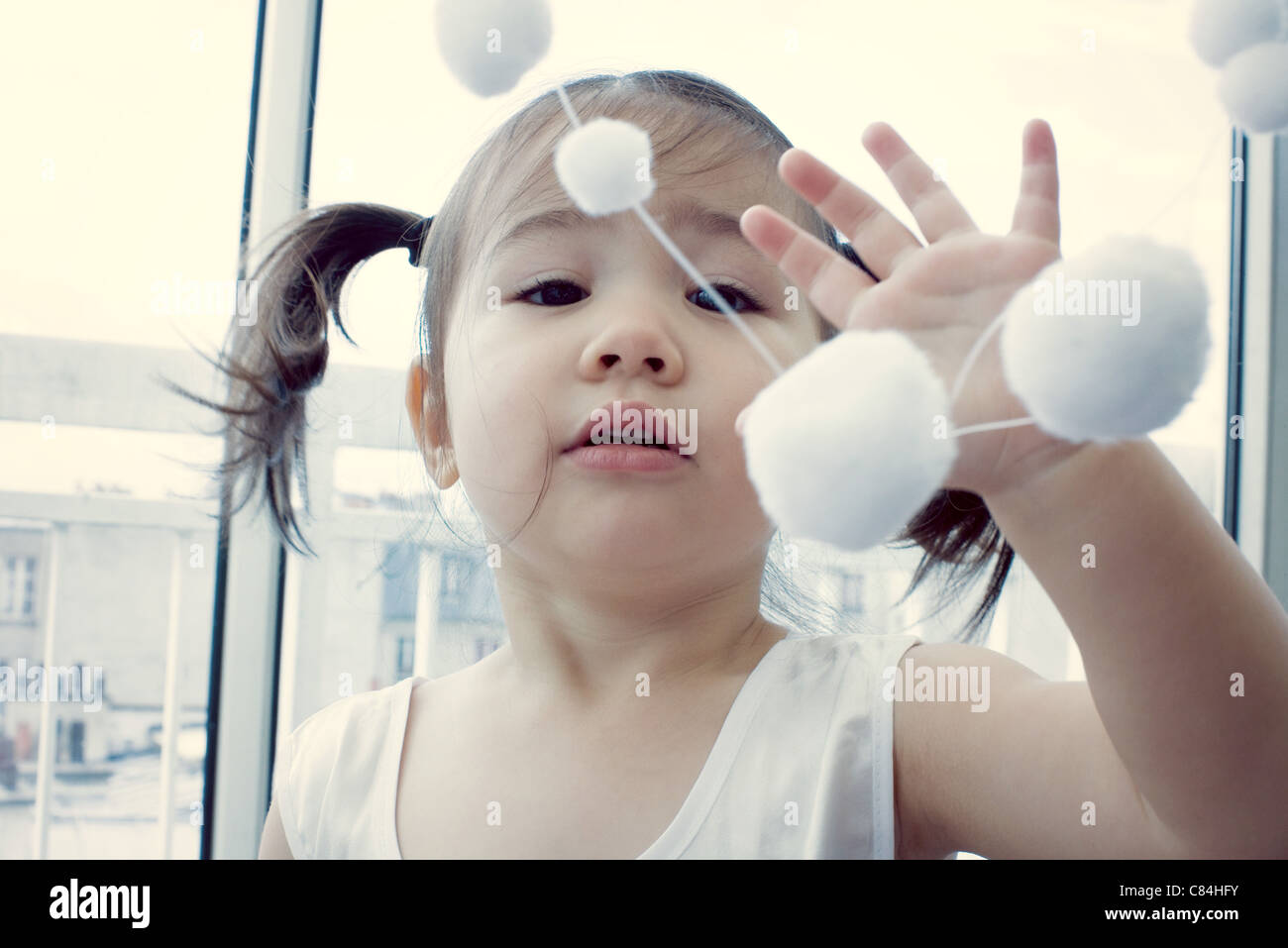 Little girl playing with hanging decoration - Stock Image