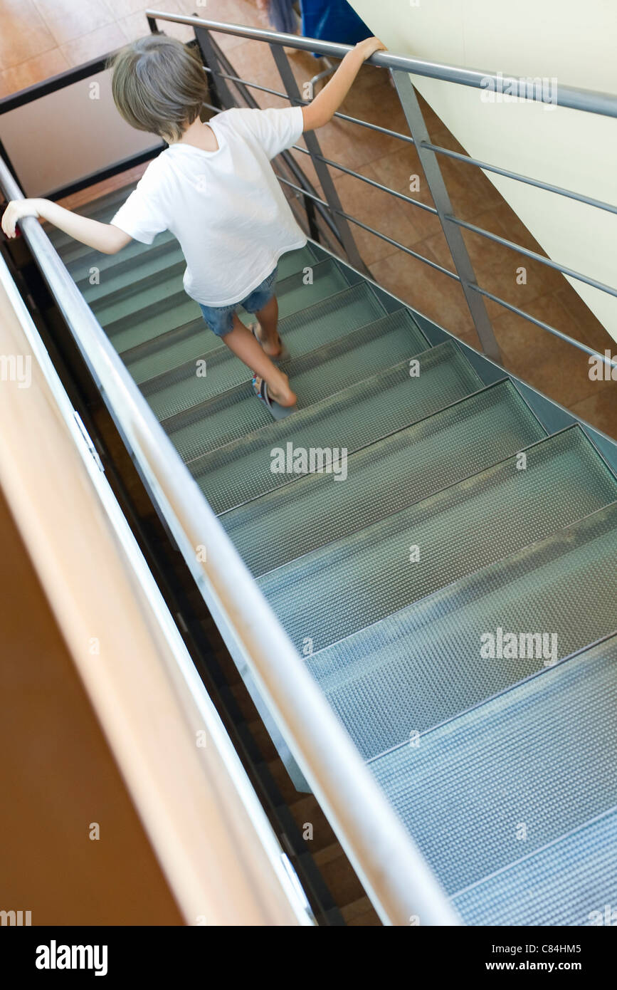 Boy going down stairs, rear view - Stock Image