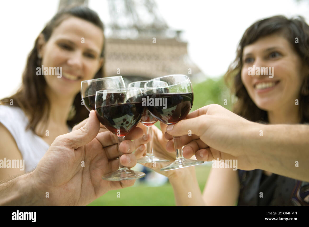 Friends clinking wine glasses outdoors - Stock Image
