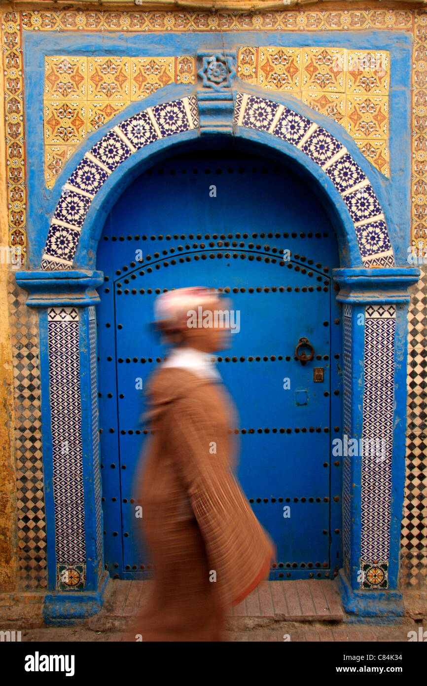 Young woman wearing a jellabah walks past a decorative wooden & tiled door in the medina/old walled town, Essaouira, - Stock Image
