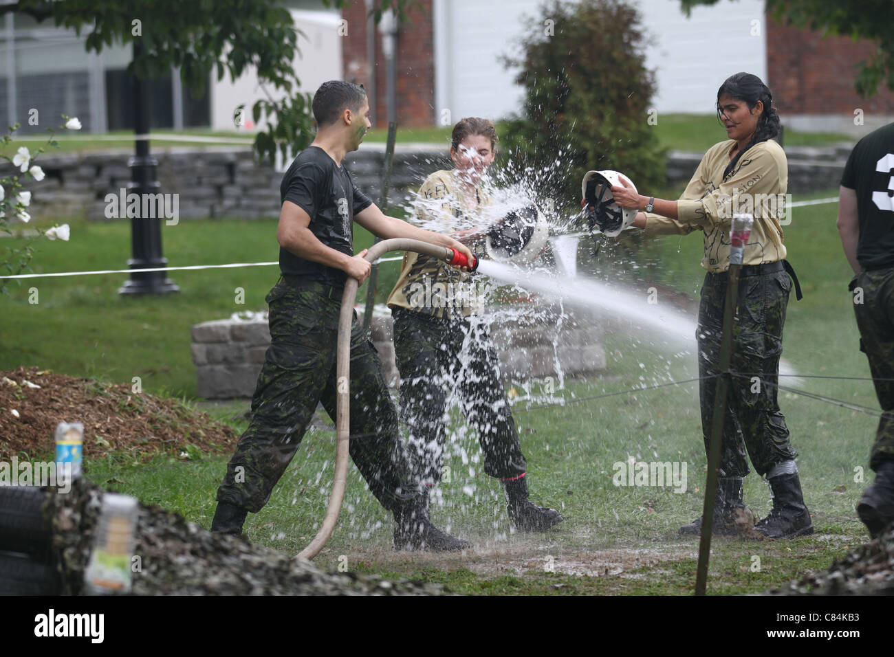 Military man spraying a fire hose, girl stopping the spray with a helmet Stock Photo