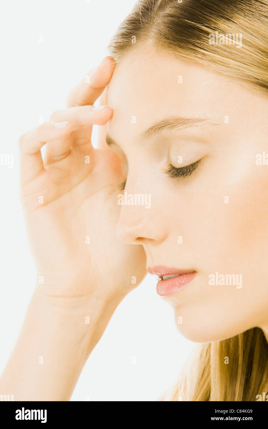 Woman with eyes closed, touching forehead, side view - Stock Image
