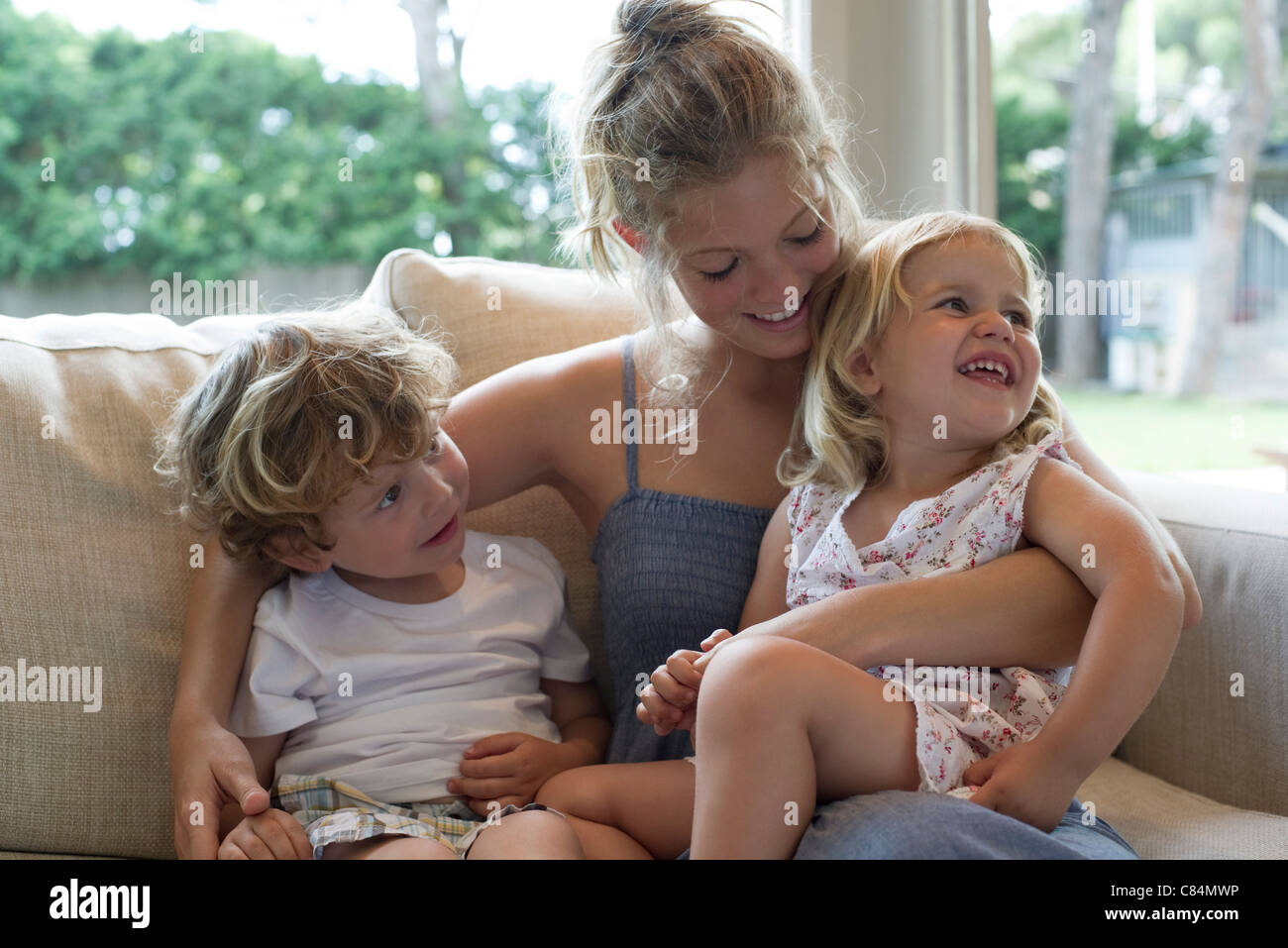 Mother and two young children cuddling on sofa - Stock Image