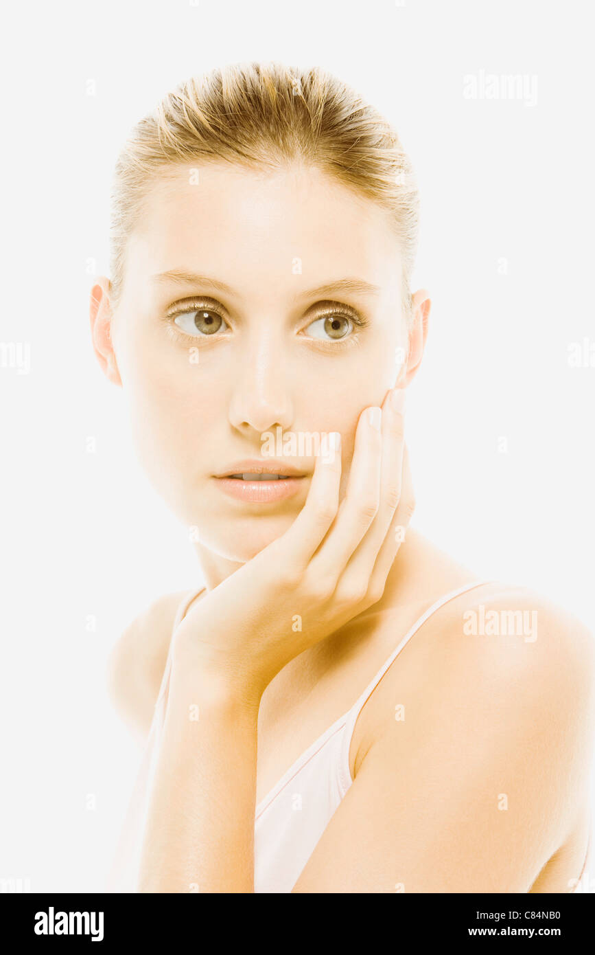 Young woman with hand under chin contemplatively looking away Stock Photo