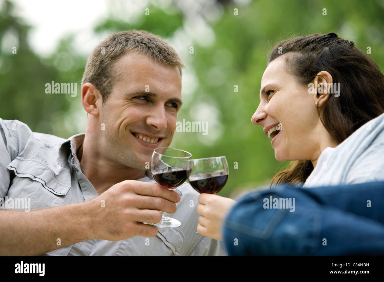 Couple clinking wine glasses outdoors - Stock Image