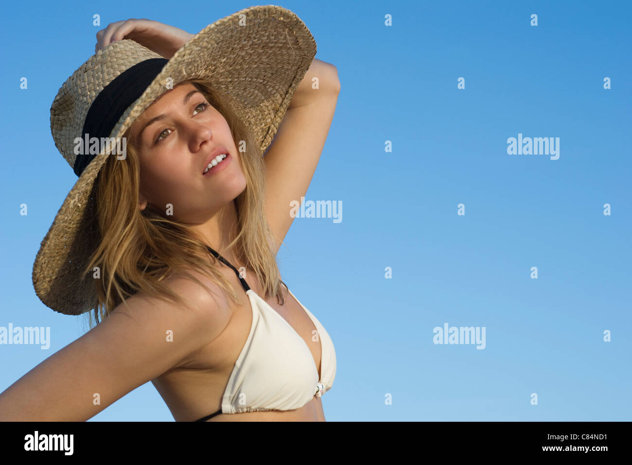 Woman wearing bikini and sun hat looking away dreamily, portrait - Stock Image