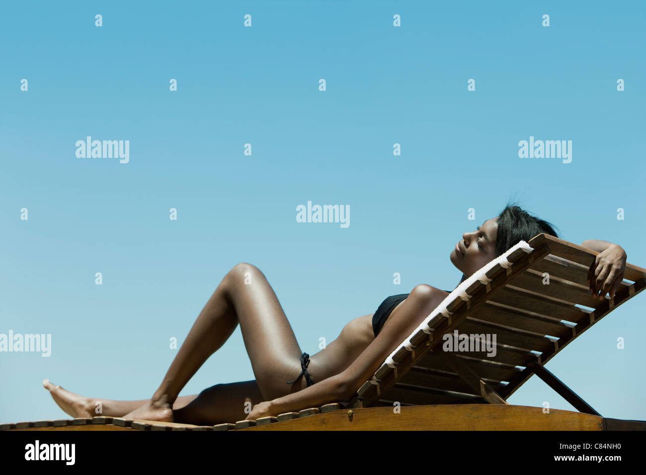 Woman relaxing on deckchair in sun - Stock Image