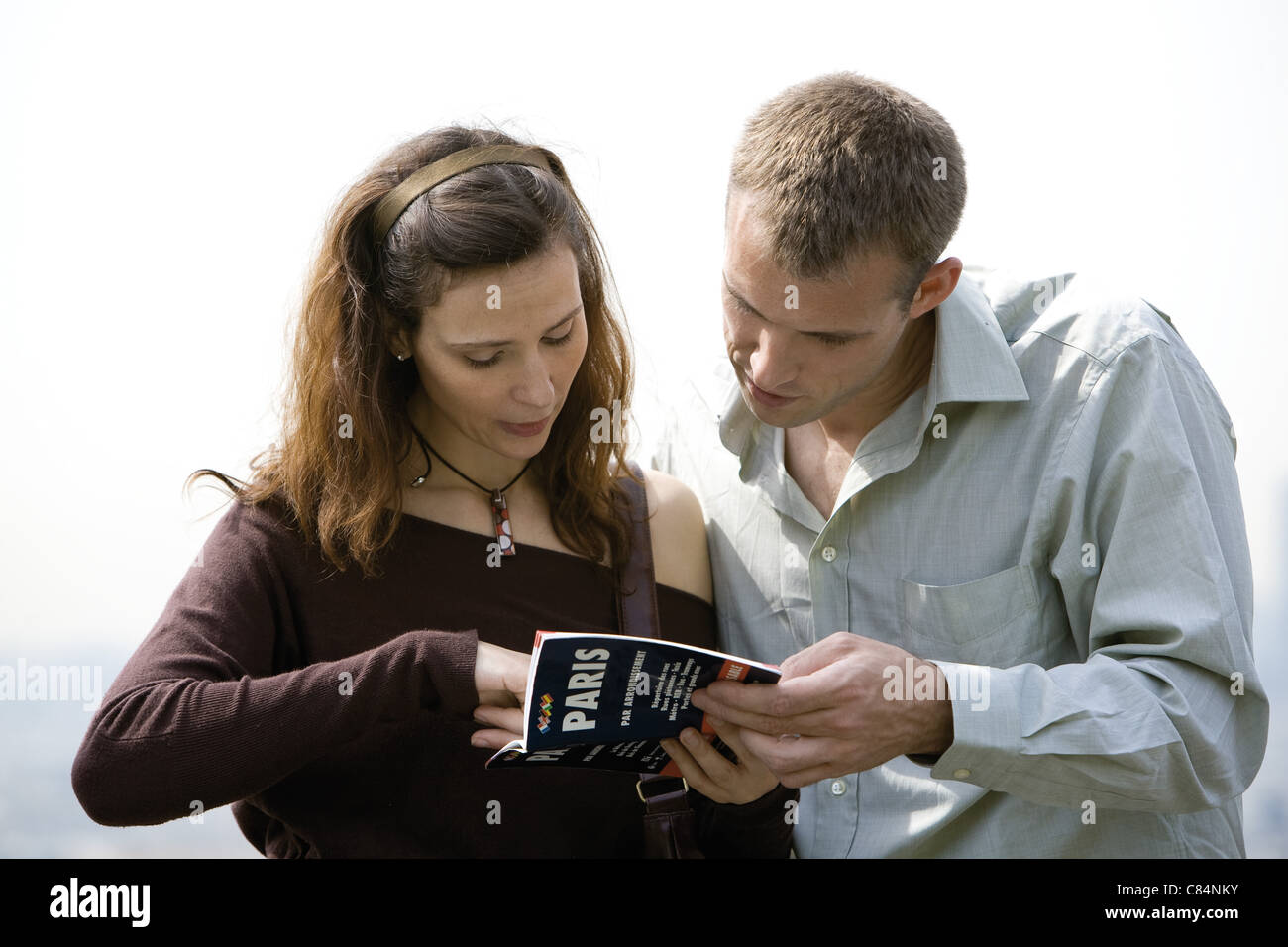 Tourist couple consulting guidebook - Stock Image