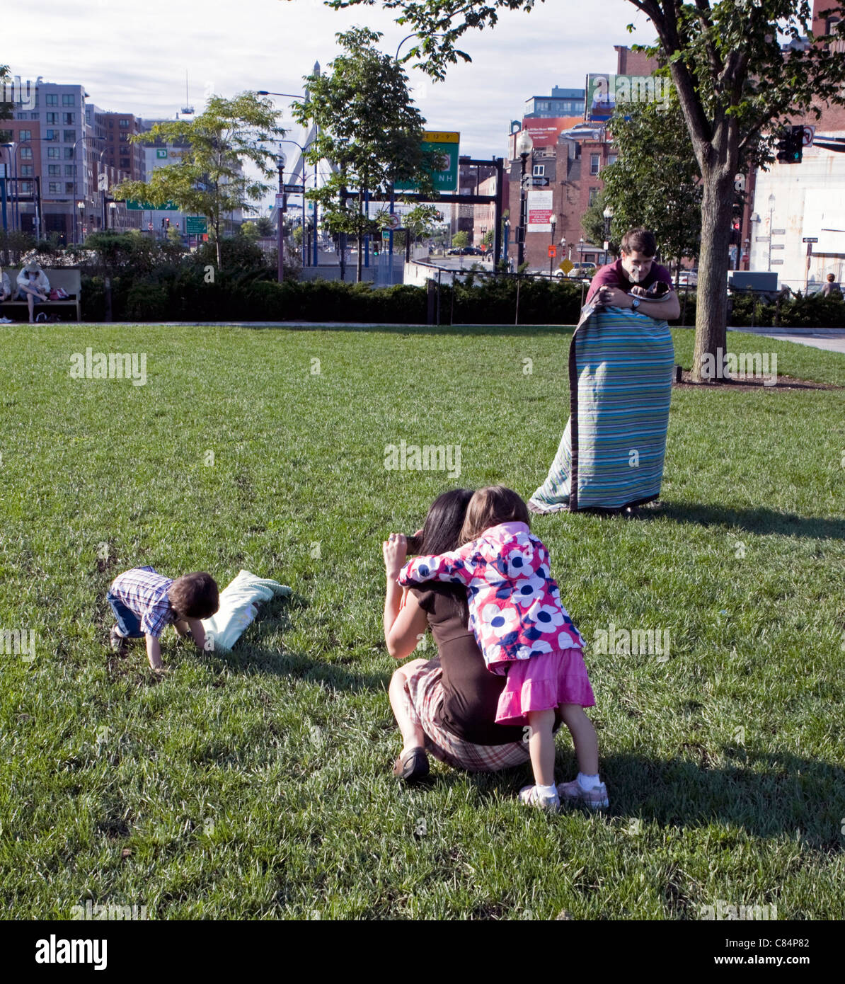 A family enjoys time together in North End Park in the Rose Kennedy Greenway in Boston. - Stock Image