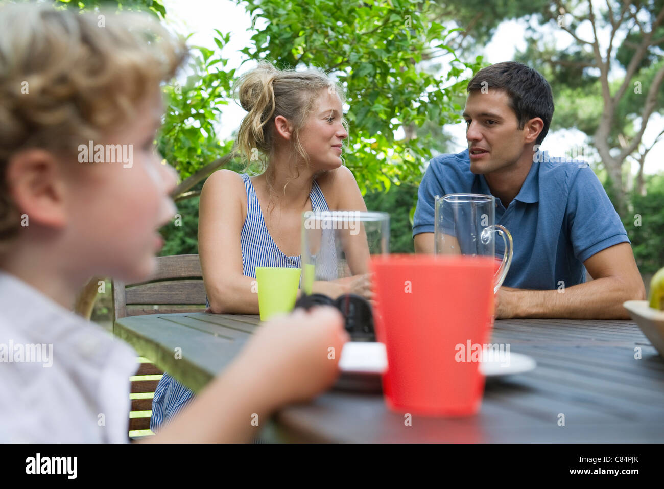 Family relaxing together at table outdoors - Stock Image