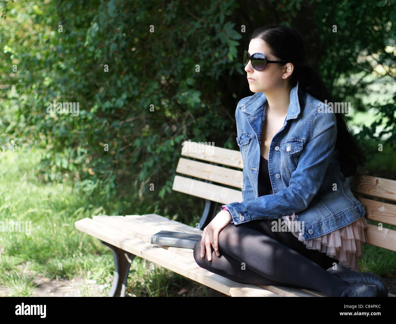 young woman with sunglasses relaxing on park bench - Stock Image