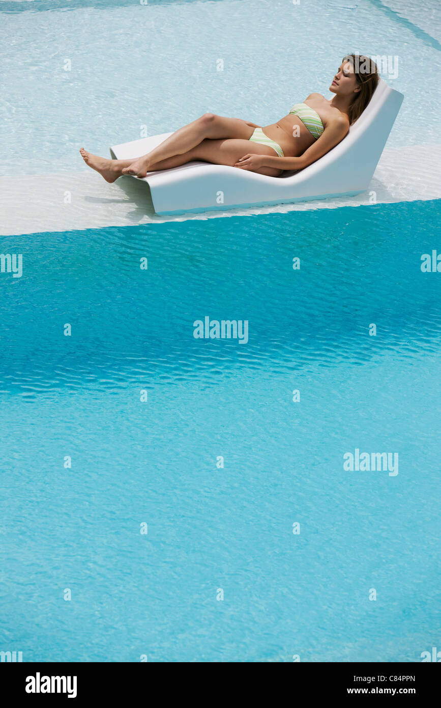 Young woman sunbathing by pool - Stock Image
