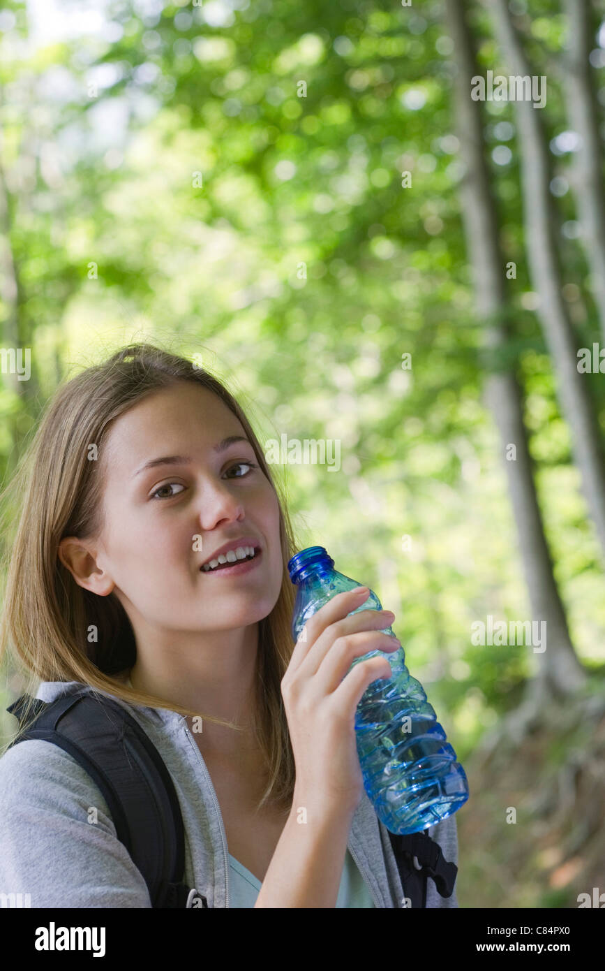 Woman holding bottled water in woods - Stock Image