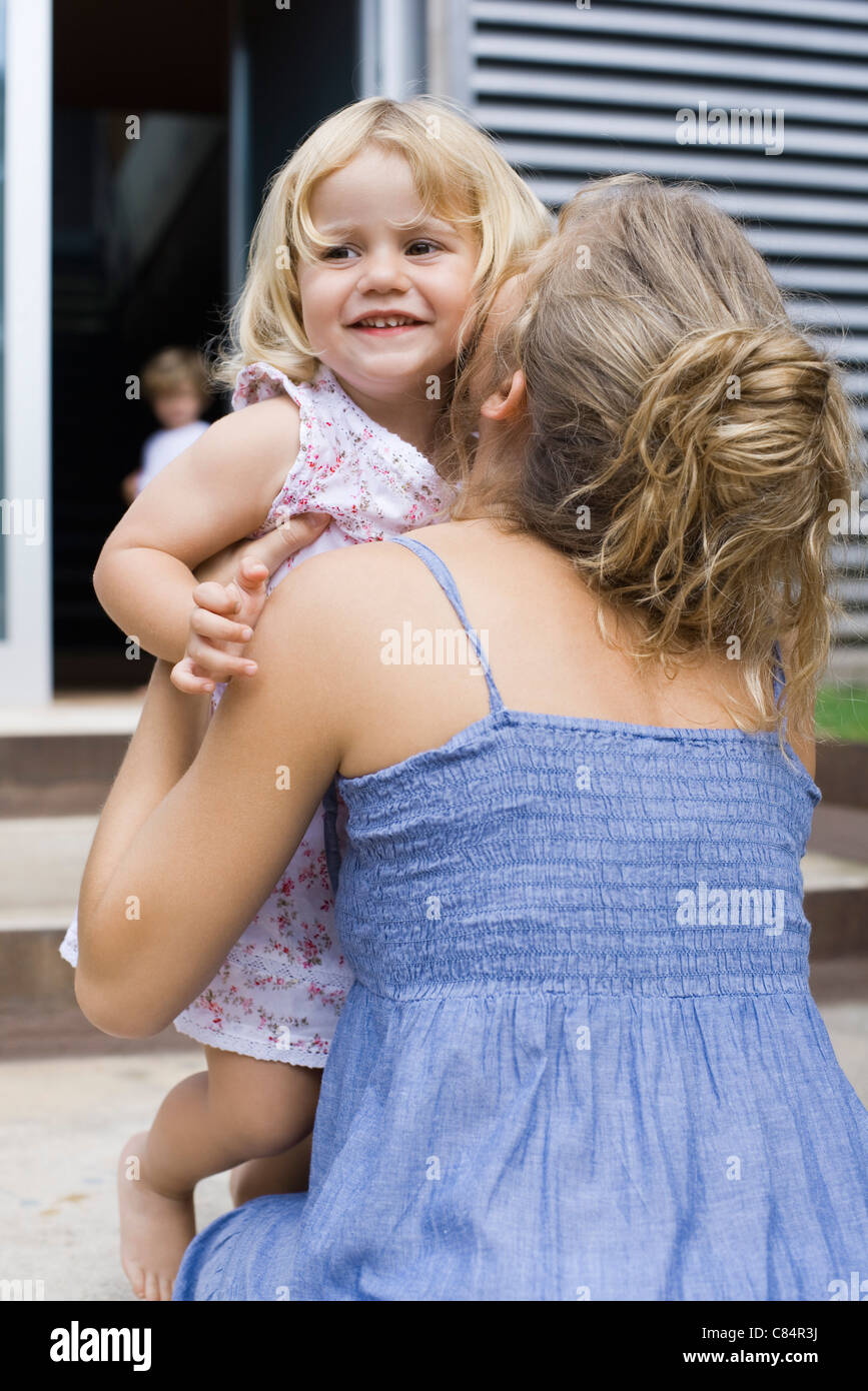 Mother embracing young daughter - Stock Image