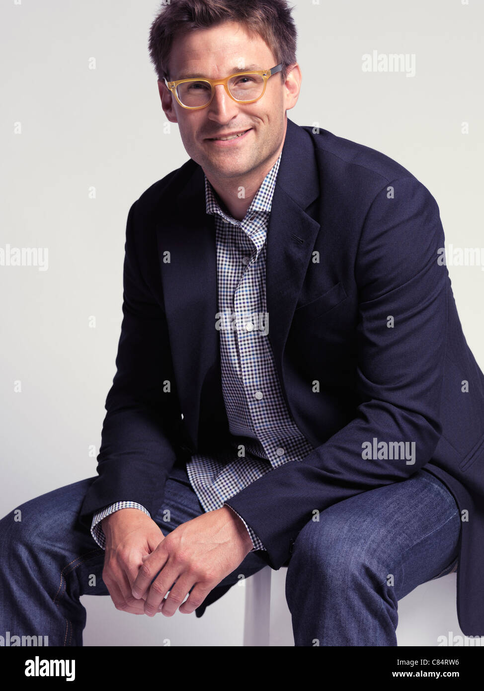 Fashionably dressed smiling man in his thirties wearing jeans and a stylish jacket - Stock Image