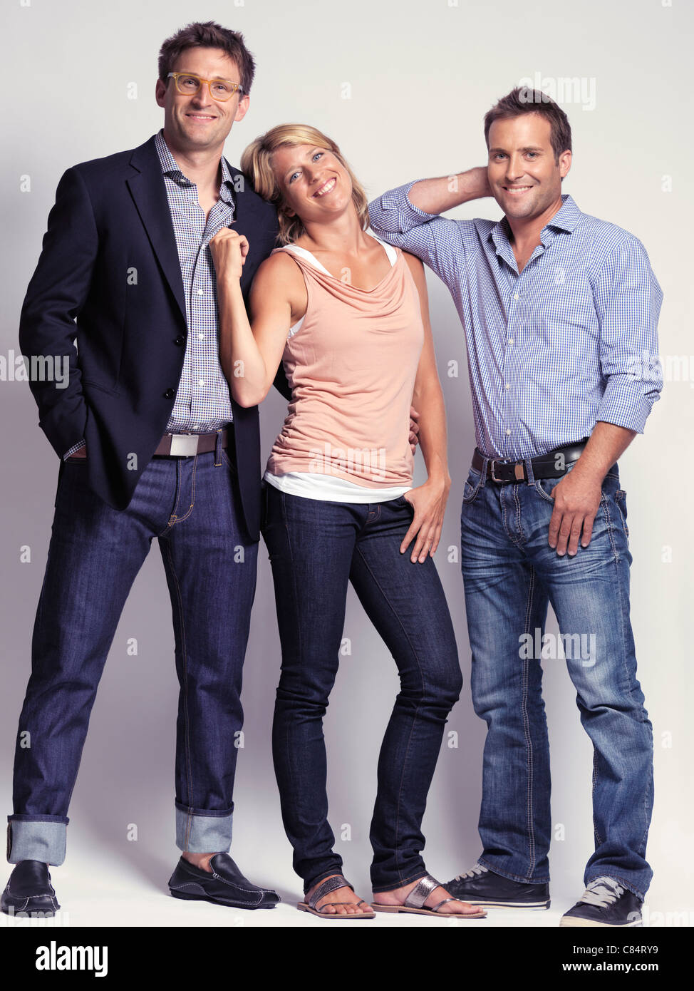 Smiling casually but with style dressed two men and a woman wearing jeans Stock Photo